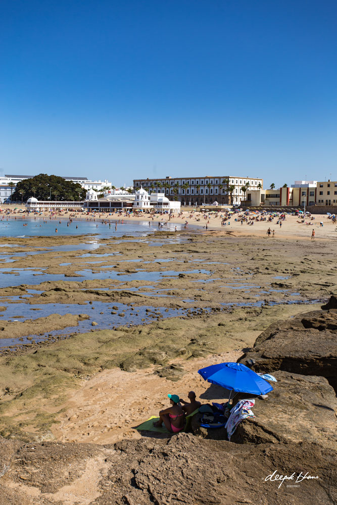 Cadiz-Spain-beach-rocks-umbrella
